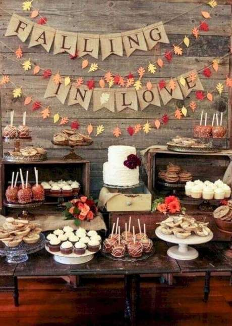 52. Noivado com decoração simples e rústica para mesa com muitos doces e bolo branco dois andares – Foto: OneWed