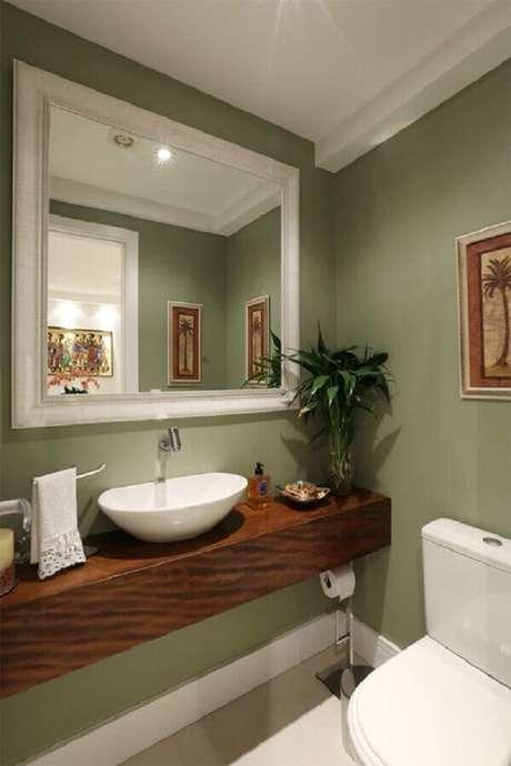24. Parede verde oliva para banheiro decorado com bancada de madeira – Foto: Casa de Valentina