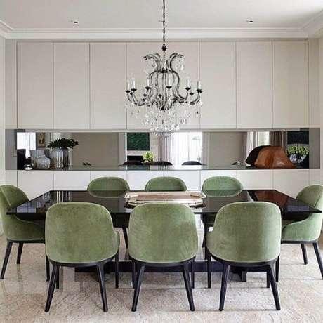 14. Sala de jantar sofisticada decorada com cadeira estofada com tecido verde oliva e lustre de cristal – Foto: Paula Magnani