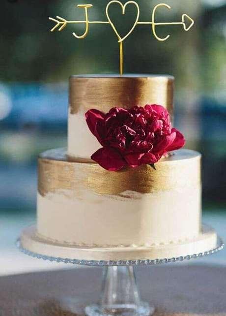 71. Os detalhes em dourado deram um toque moderno ao bolo de noivado simples decorado com uma única flor marsala – Foto: Weddbook
