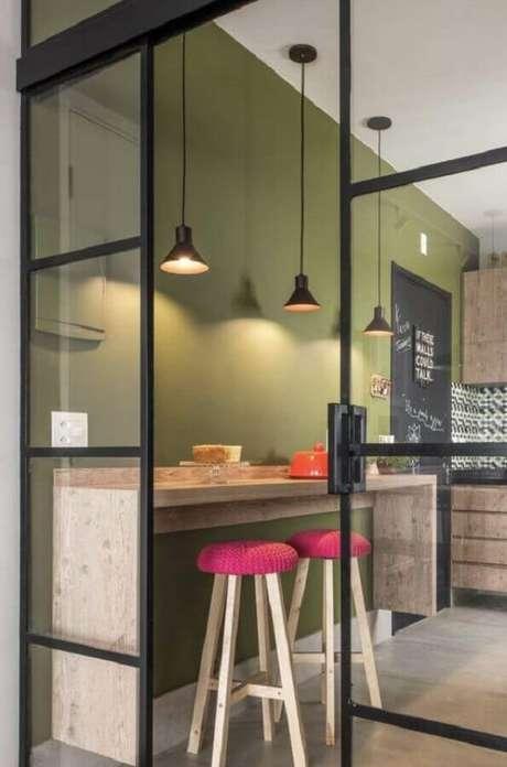 58. Tinta verde oliva para parede de cozinha com bancada de madeira – Foto: Decostore