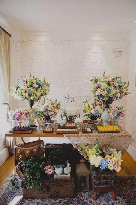 44. Linda decoração de noivado simples com arranjos de flores e maleta antiga sobre bau de madeira – Foto: Home Decoo