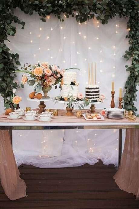 78. Decoração de noivado simples com arranjos de flores para mesa e folhagens para painel – Foto: iCasei
