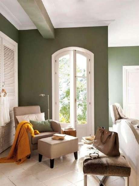 20. Cada decorada com poltrona bege e tinta verde oliva para parede – Foto: El Mueble