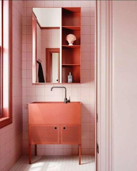 15. Banheiro decorado com gabinete na cor coral e revestimento rosa claro – Foto Casa BVogue