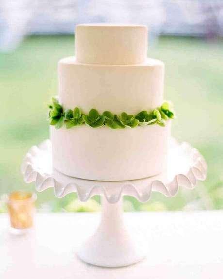 27. Lindo bolo de noivado simples todo branco com arco de flores verdes – Foto: Once Wed