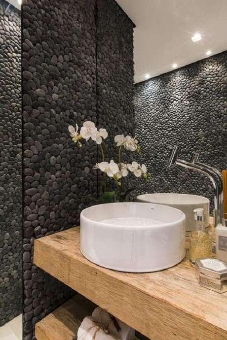 28. Revestimento de pedra feito com seixos pretos valoriza a decoração desse banheiro. Fonte: Pinterest