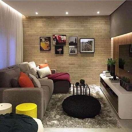 46. Puff preto redondo para decoração de sala de TV com parede tijolinho – Foto: Pinterest