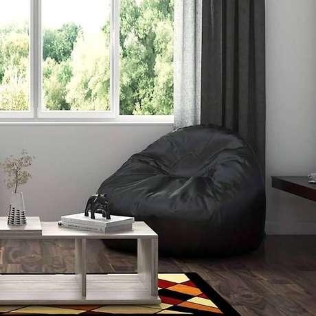 49. Decoração de sala com tapete colorido e puff fofão preto – Foto: Pinterest