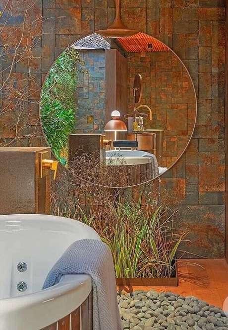9. Decoração de banheiro com banheira, espelho redondo e revestimento de pedra ferro. Fonte: Mister Cryl Tintas