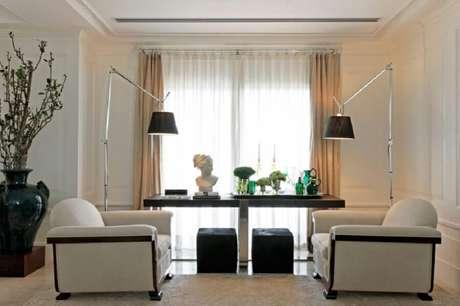 23. Sala decorada com poltronas brancas e puff preto quadrado – Foto: Roberto Migotto