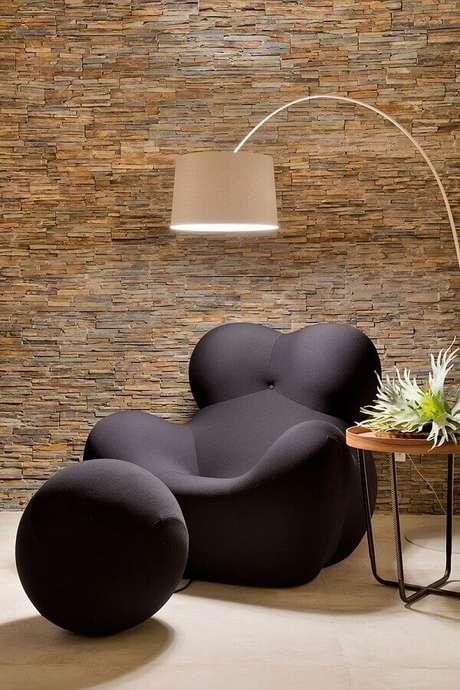 18. Decoração com parede rústica e poltrona moderna com puff preto redondo – Foto: Casa de Valentina