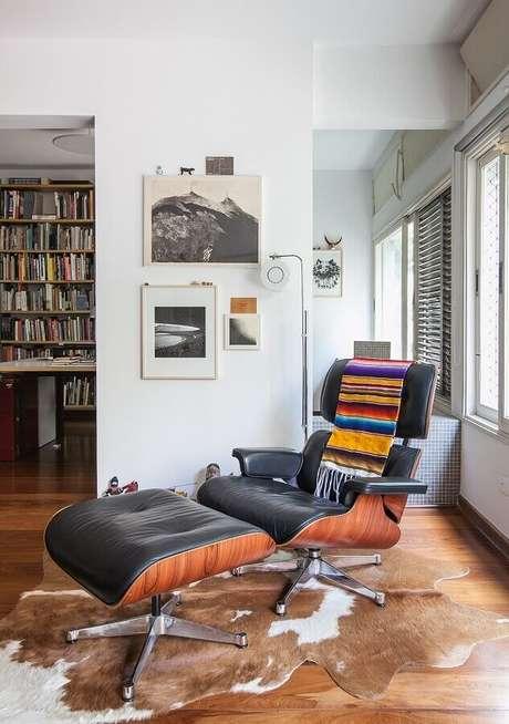 5. Decoração com tapete de couro e puff preto para poltrona confortável – Foto: Histórias de Casa