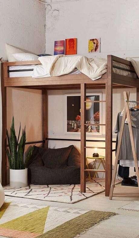 9. Decoração de quarto simples com puff fofão preto embaixo de cama suspensa – Foto: Jeito de Casa
