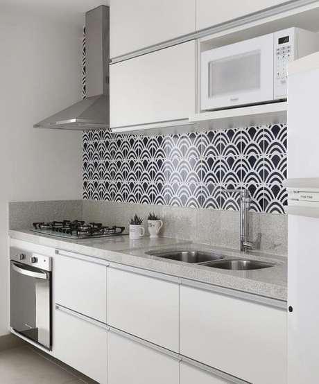 44. Armário basculante com acabamento branco e revestimento de parede estampado decoram a cozinha. Fonte: Pinterest