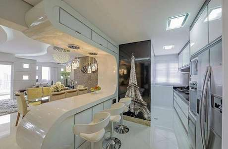 40. Balcão de cozinha com design surpreendente conta com armário basculante na parte superior. Projeto Iara Kilaris