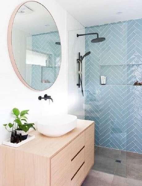 49. Gabinete de madeira clara para decoração de banheiro azul e branco com espelho redondo – Foto: Micasa Revista