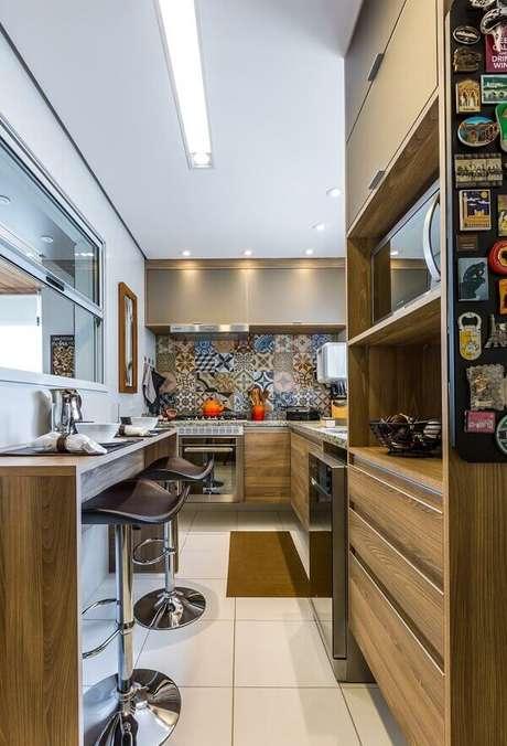 37. Cozinha em l pequena com armário basculante suspenso e ladrilho hidráulico. Fonte: By Arq&Design
