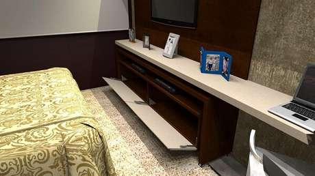 48. A porta basculante armário conta com uma abertura inteligente e otimiza o espaço do quarto. Projeto por Rafael Cunha