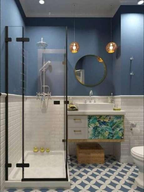 32. Decoração de banheiro azul e branco com gabinete suspenso e espelho redondo – Foto: Pinterest
