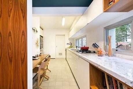 38. Cozinha com tampo de mármore e armário basculante que se estende por todo o ambiente. Projeto por DT Estudio Arquitetura