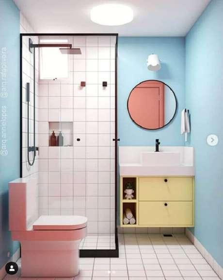 13. Decoração de banheiro azul com gabinete amarelo e vaso cor de rosa – Foto: Pinterest