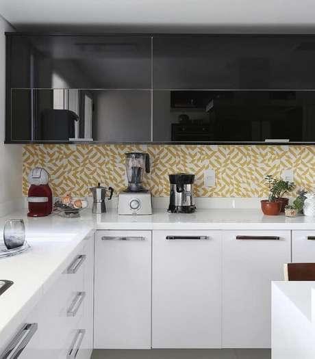 19. O armário basculante de cozinha preto se harmoniza com o revestimento de parede amarelo. Fonte: Pinterest