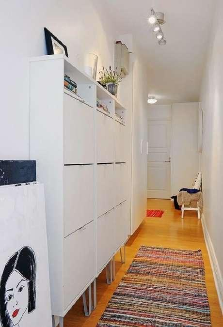 41. Armário basculante decora o corredor do imóvel e ajuda na organização de itens. Fonte: Casa de Amados
