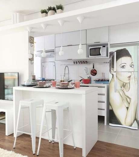22. O armário basculante cozinha branco traz neutralidade para o espaço com geladeira adesivada. Fonte: Pinterest