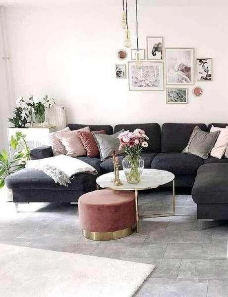 53. Sala decorada com sofá preto e mesa de centro redonda branca com estrutura dourada – Foto: Pinterest
