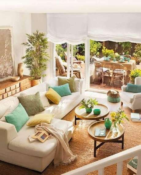 55. Mesa de centro redonda de madeira para sala de estar decorada com almofadas coloridas – Foto: Jeito de Casa