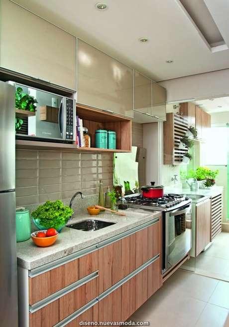 53. Cozinha com revestimento bege e armário de madeira – Foto Casa Abril