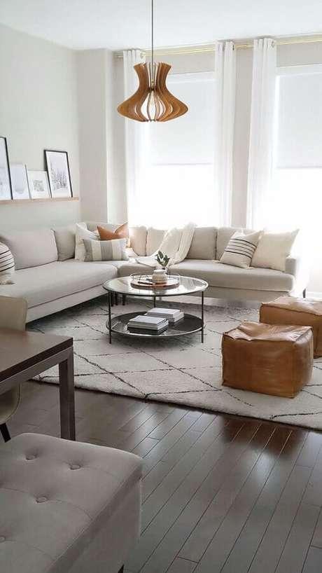 16. Decoração clean para sala com sofá de canto grande e mesa de centro redonda – Foto: Decoholic