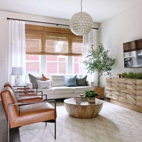 36. Mesa de centro redonda de madeira para sala de estar decorada com lustre redondo e poltrona de couro moderna – Foto: Serena & Lily