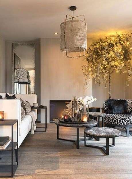48. Mesa de centro redonda dupla para sala de estar decorada com lustre rústico e sofá branco – Foto: Kenay Home