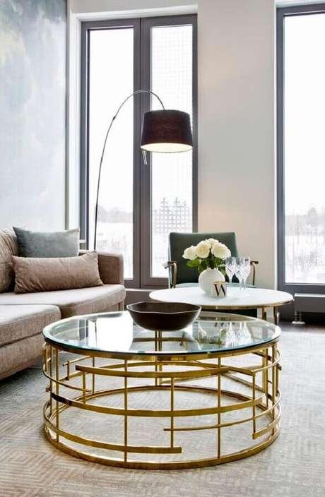 49. Sala de estar decorada com mesa de centro redonda de vidro com estrutura dourada – Foto: Homedit