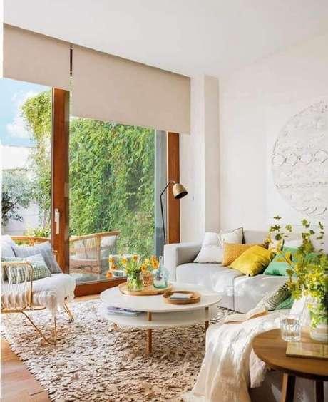 32. Mesa de centro redonda branca para decoração de sala com tapete felpudo e almofadas coloridas – Foto: Editions de l'Arkhan