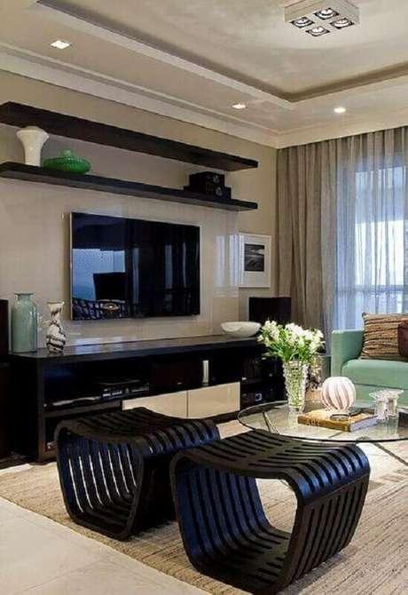 37. Mesa de centro redonda de vidro para sala de TV decorada com puff preto moderno – Foto: Jeito de Casa