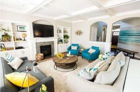 35. Sala decorada com poltrona azul e mesa de centro redonda de madeira – Foto: Pinterest
