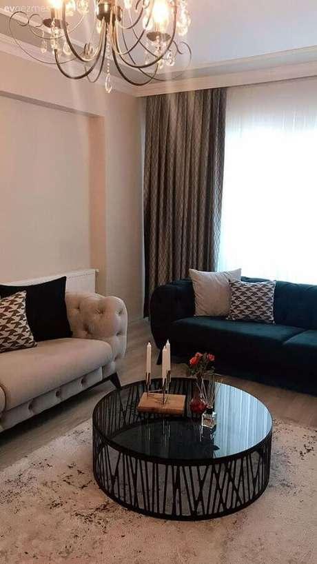 51. Sala de estar decorada com sofá capitonê e mesa de centro redonda preta – Foto: Fancy House Design