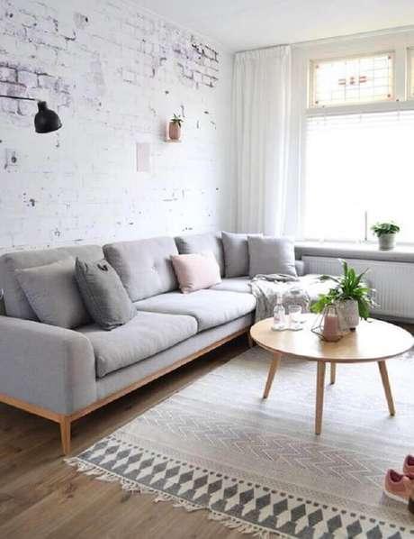 56. Sala minimalista decorada com sofá cinza claro e mesa de centro redonda de madeira – Foto: Casa de Valentina