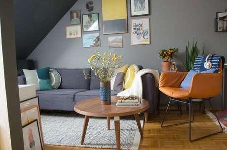 5. Mesa de centro redonda de madeira para sala cinza decorada com poltrona de couro marrom – Foto: Houzz