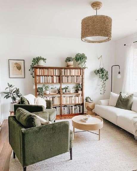 34. Decoração de sala com estante de livros, poltronas verdes e mesa de centro redonda de madeira – Foto: Apartment Therapy
