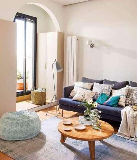 59. Sala simples decorada com mesa de centro redonda de madeira e sofá azul marinho – Foto: El Mueble