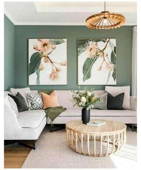 60. Mesa de centro redonda de madeira para decoração de sala verde com sofá de canto – Foto: Jeito de Casa