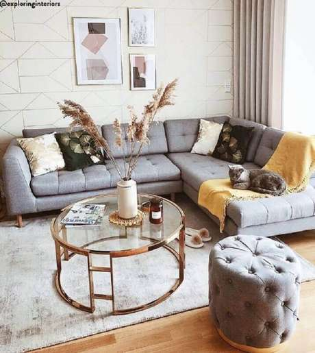 38. Mesa de centro redonda de vidro para sala de estar decorada com sofá de canto e puff cinza capitonê – Foto: Jeito de Casa