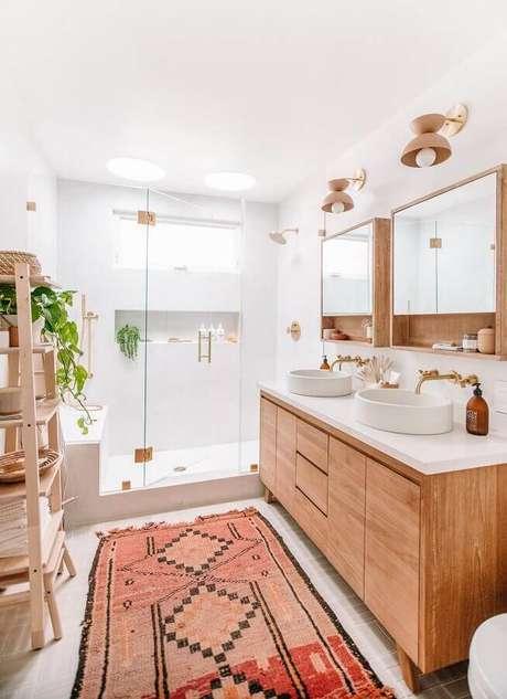 40. Decoração clean com gabinete de madeira e luminária de parede para banheiro – Foto: Apartment Therapy