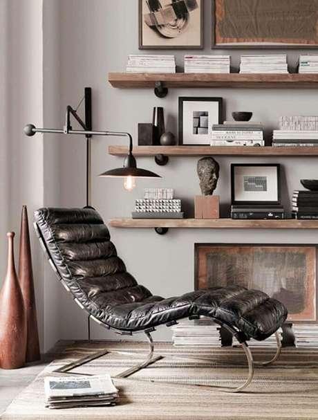 45. Luminária de parede para leitura em sala decorada com confortável poltrona preta de couro – Foto: Archzine