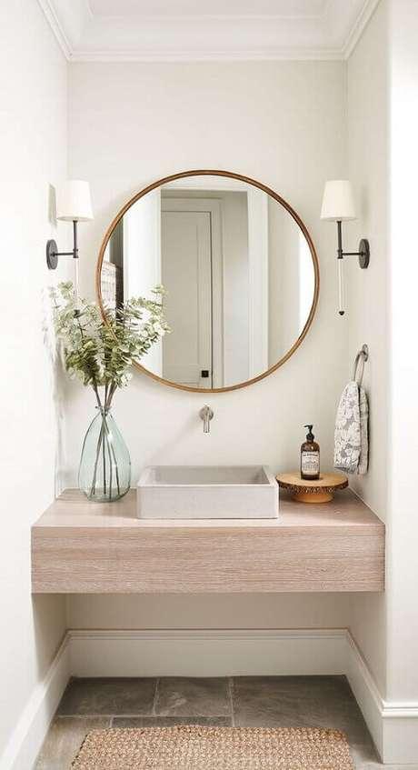 44. Decoração com bancada de madeira e luminária de parede para banheiro – Foto: Home Bunch