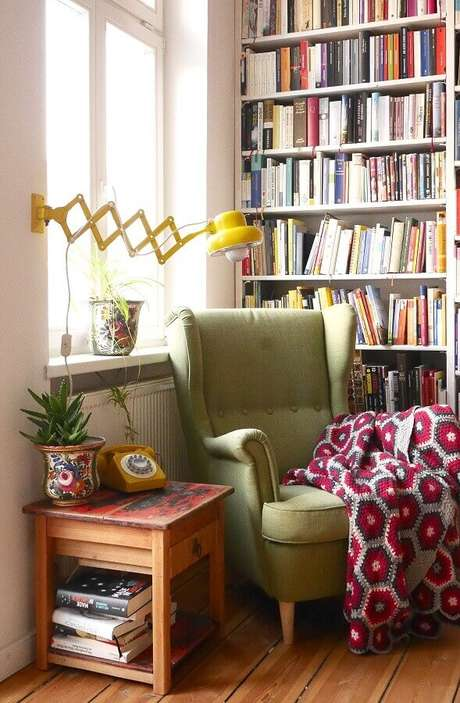 14. Luminária de parede para leitura em cantinho decorado com estante de livros e poltrona verde – Foto: Pinterest